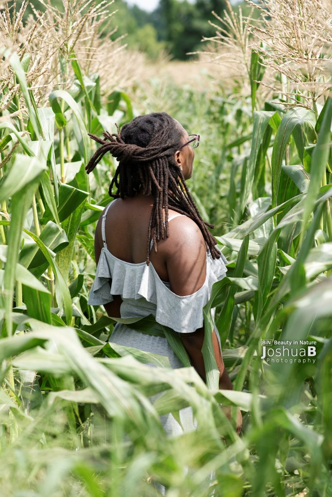 Woman with dreadlocks in cornfield