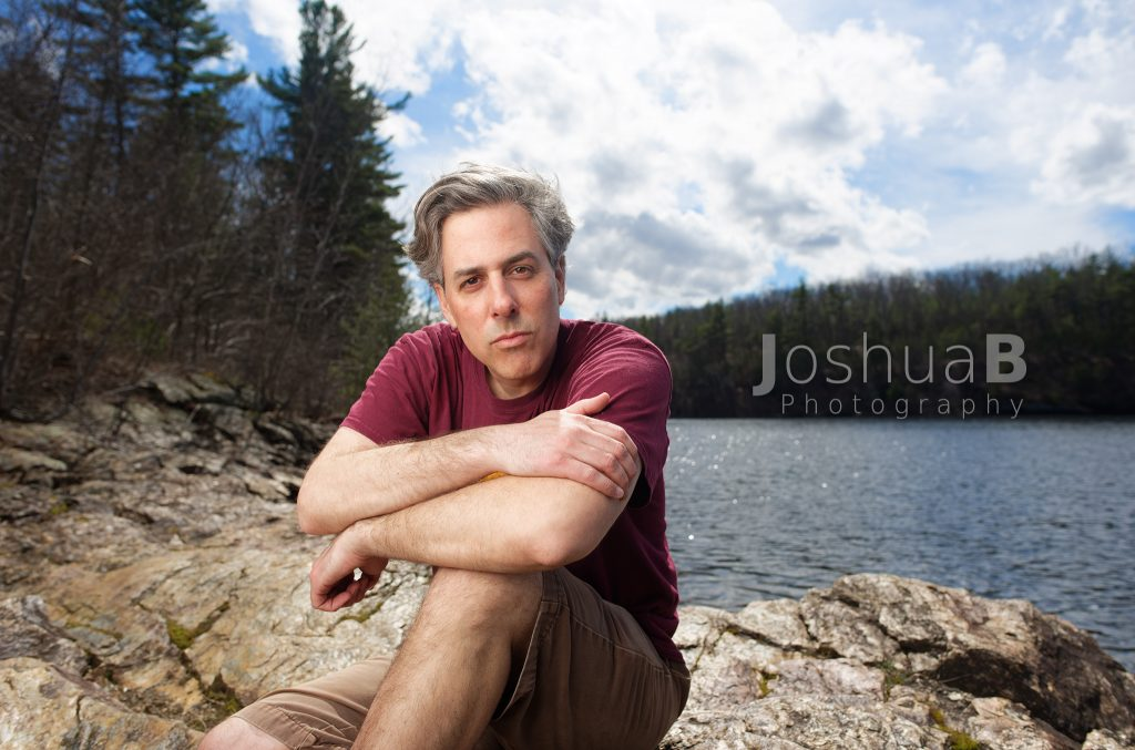man on the Wachusett Reservoir's rocky coast