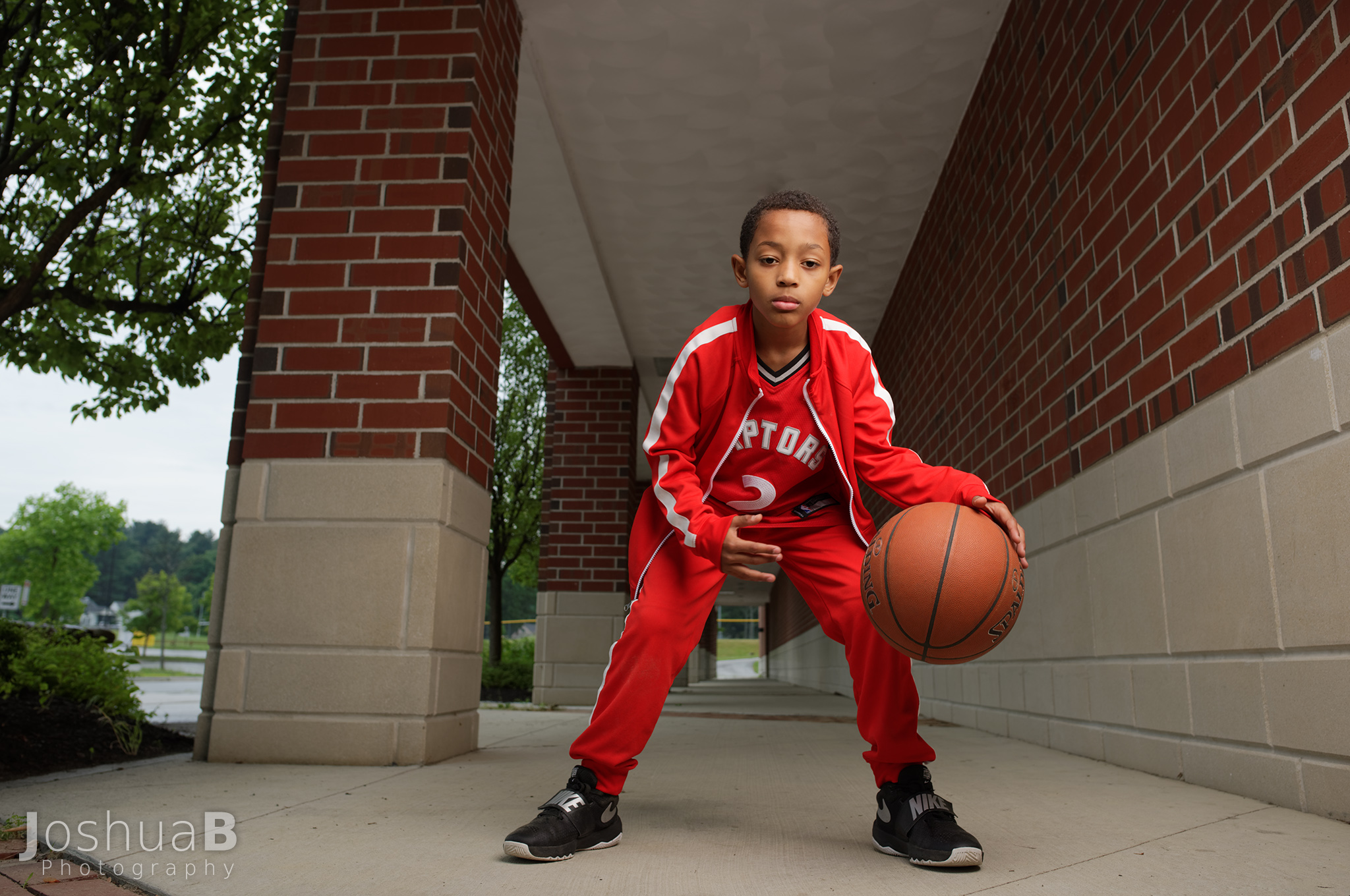 boy in red track suit and Kawhi Leonard jersey dribbling basketball at a school