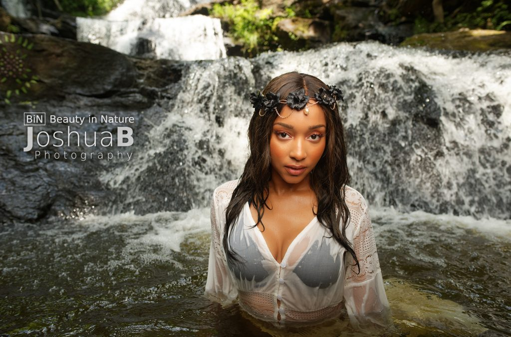 beautiful black woman in bikini and dress wet in waterfall