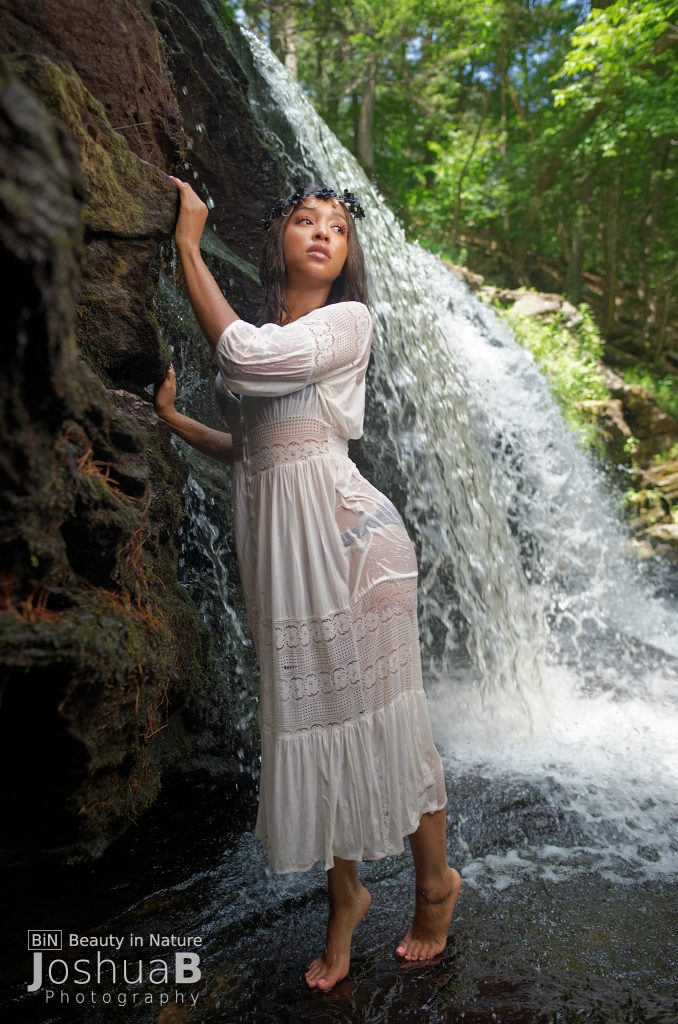 beautiful black woman in white dress at waterfall