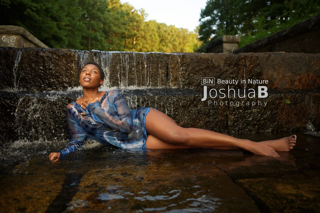 Black woman short hair lying in waterfall