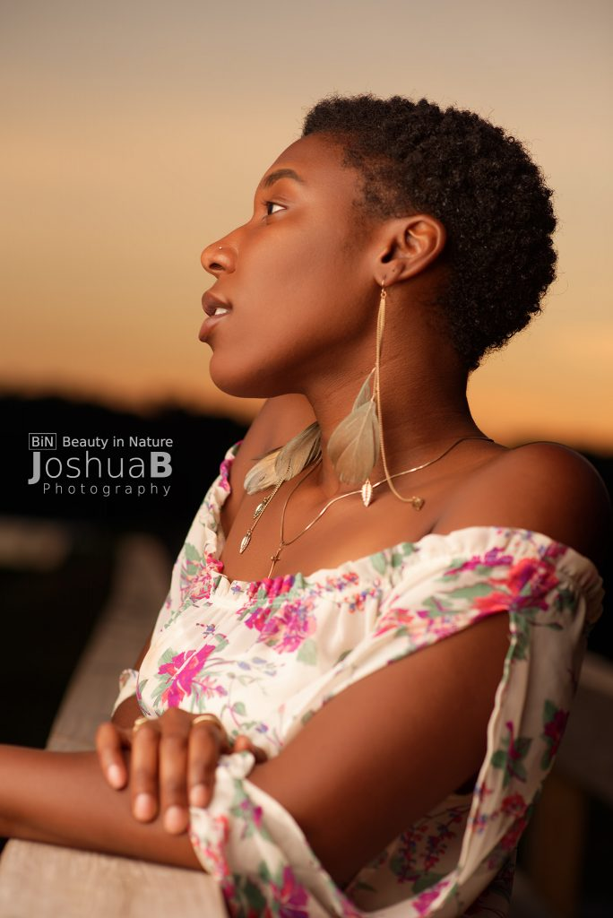 Beautiful black woman with short hair wearing summer dress at sunset