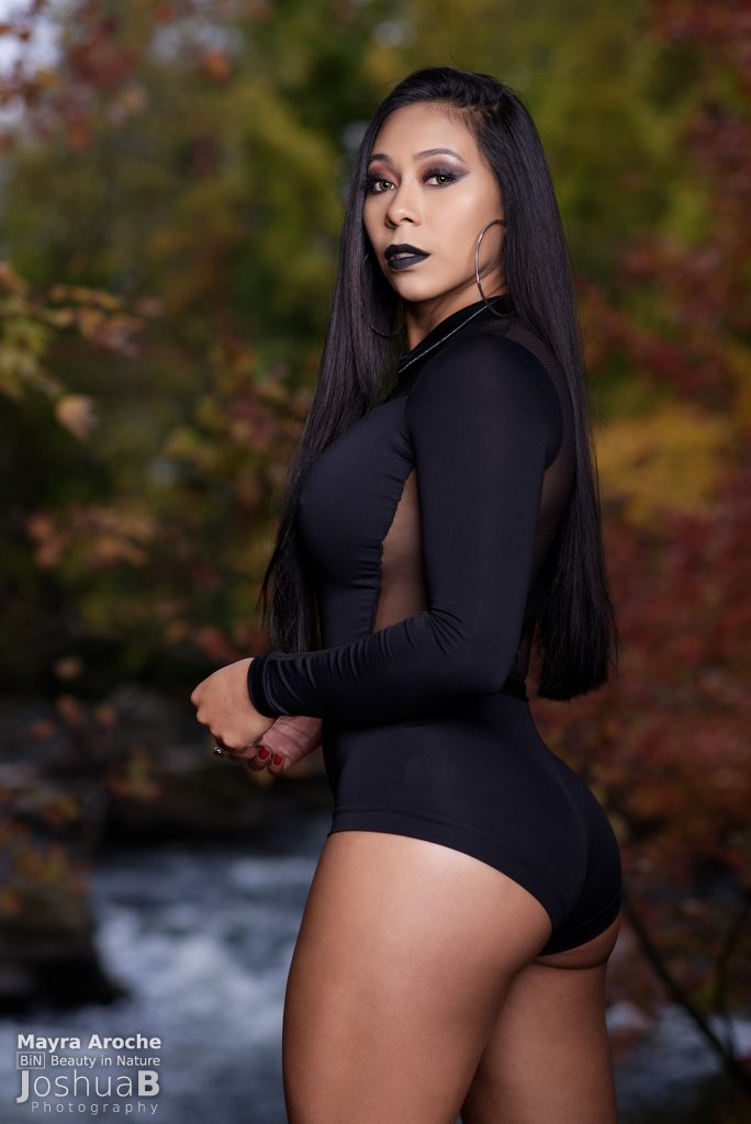 Sexy Latina from behind in Addams Family Halloween cosplay in fall foliage
