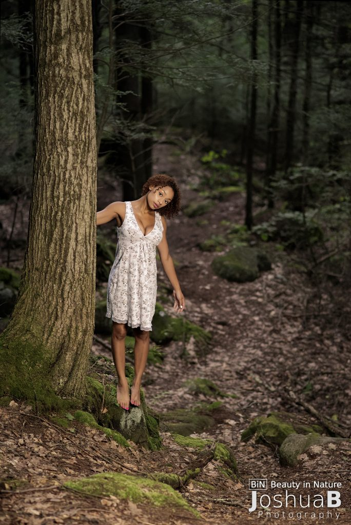 Beautiful Latina alone in the woods at night, in flower dress
