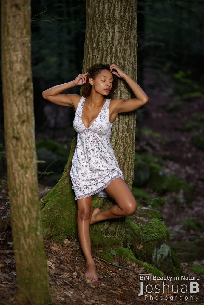 Beautiful Latina alone in the woods in dress