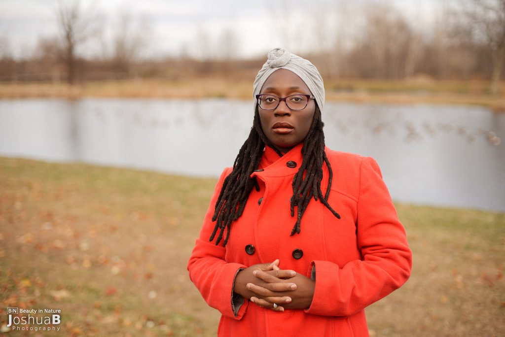 Black woman with dreadlocks in red coat in front of water with geese
