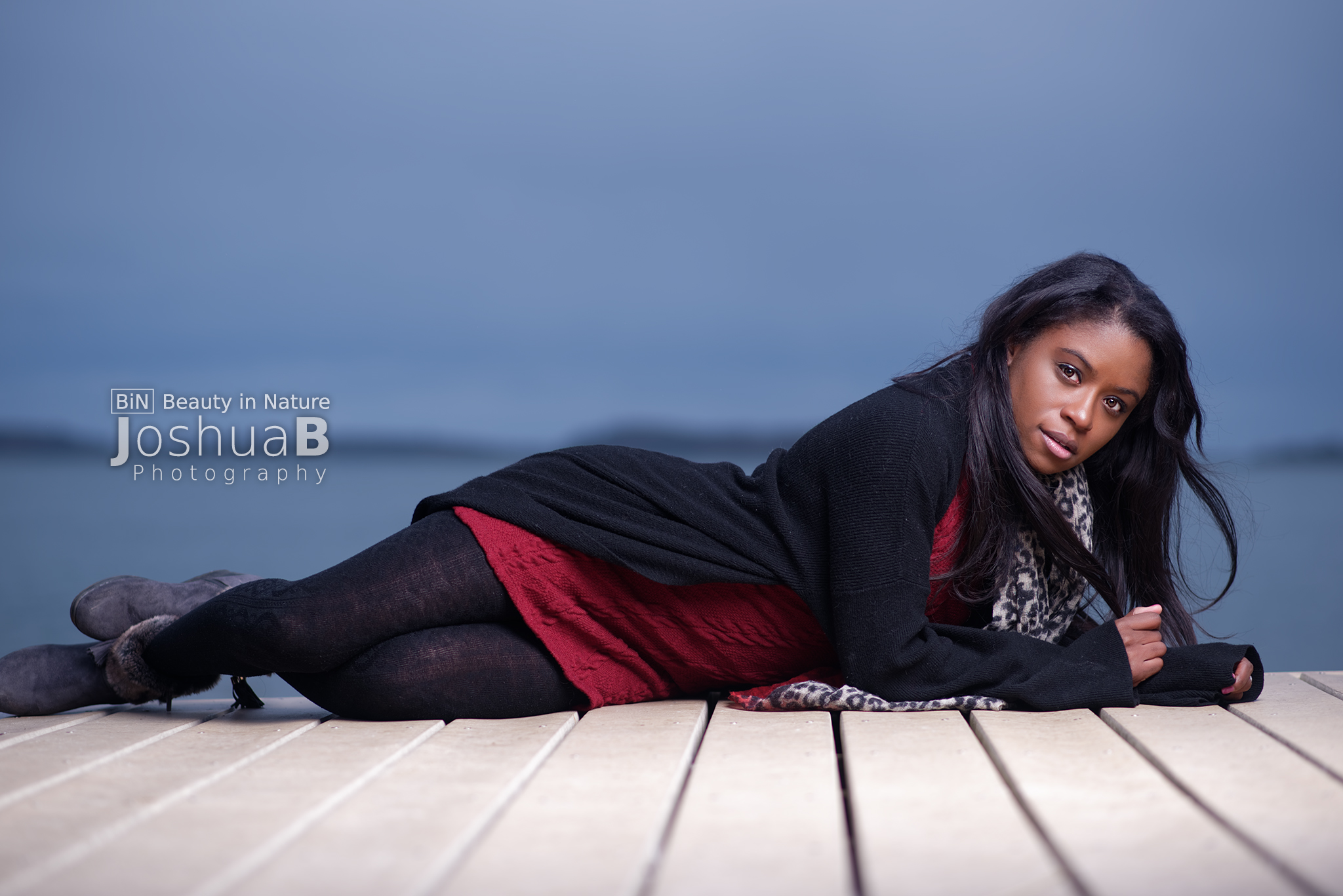 Beautiful young black woman modeling on boardwalk at Carson Beach in Boston