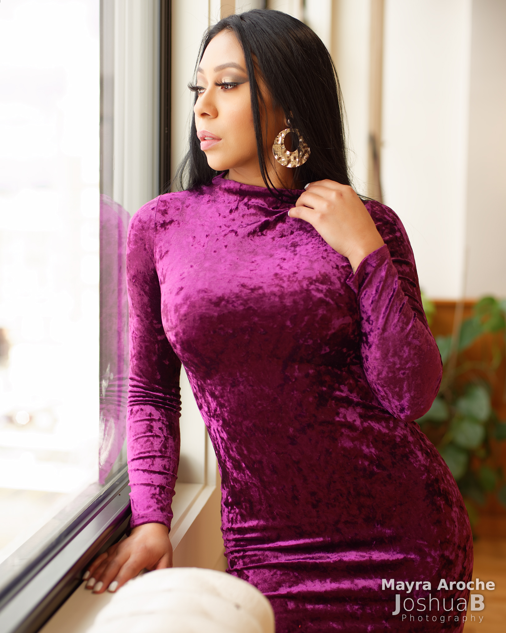 Mayra Aroche modeling at window in purple dress