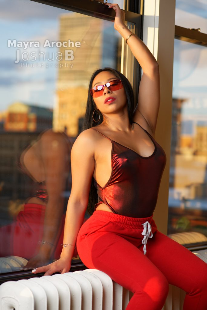 Mayra Aroche posing at window in red bodysuit sweat pants unglasses