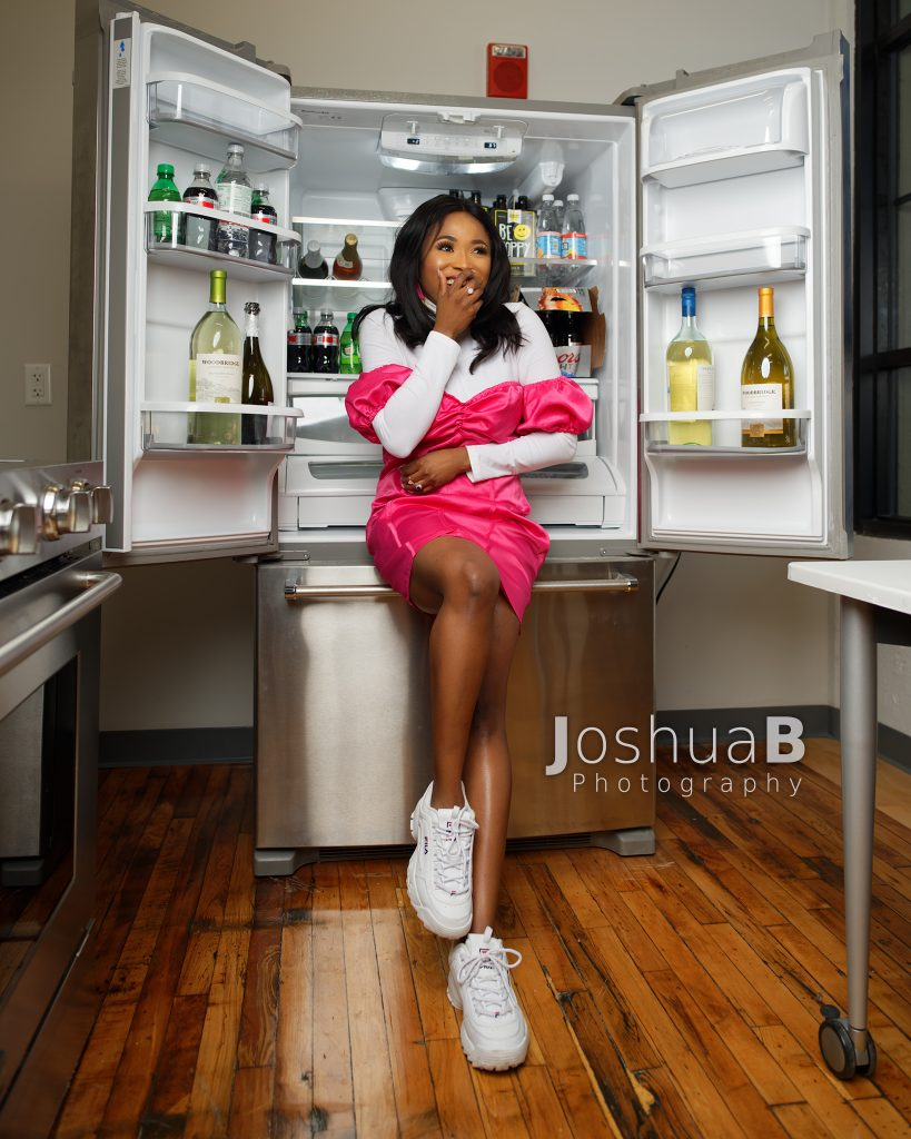 Abidemi Oke in pink and white modeling in open refrigerator surprised